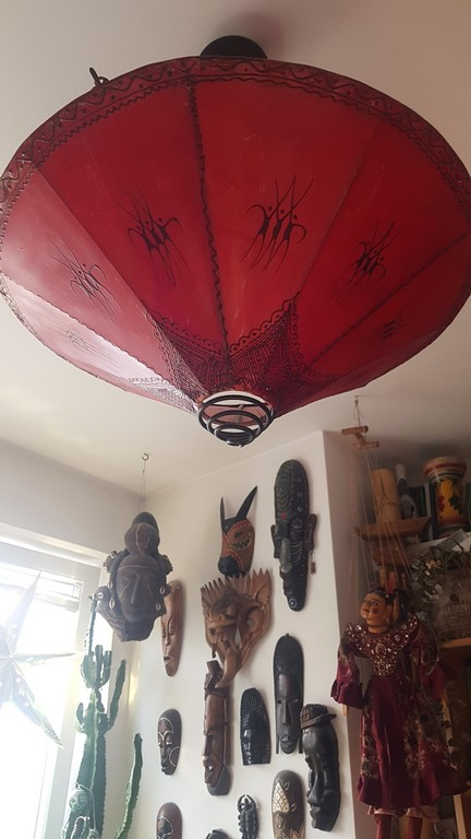 Duża, czerwona lapma zwisająca z sufitu. W tle ściana z wiszącymi maskami z całego świata