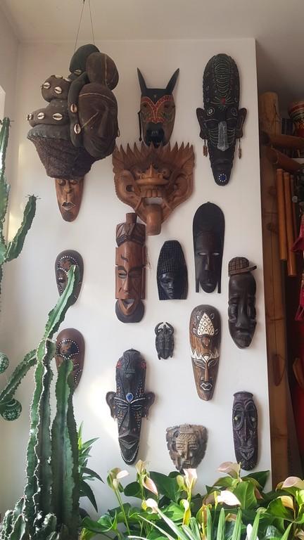 ściana z wiszącymi maskami z całego świata