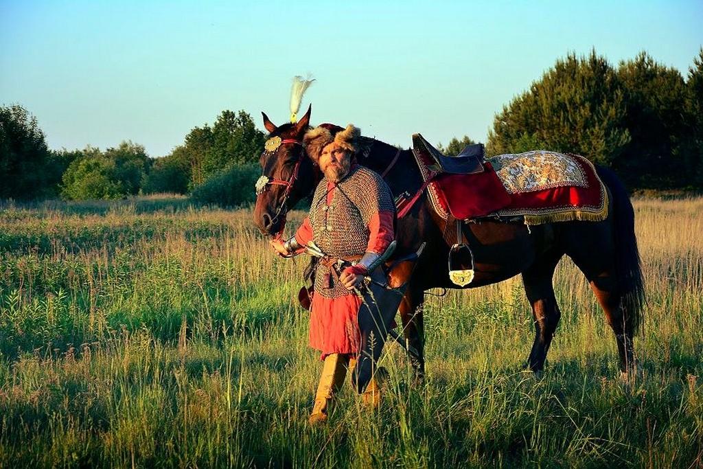 Mężczyzna w stroju historycznym, stojący na trawie przy brązowym koniu. W tle zielone pola.