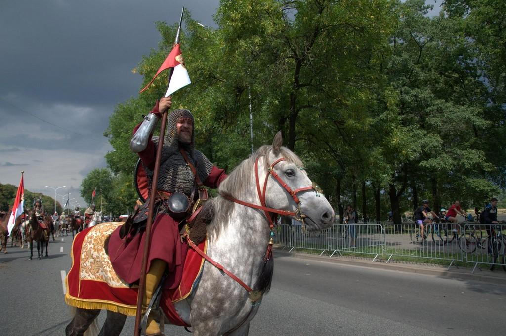 Rekonstrukcja historyczna. Mężczyzna w historycznym stroju siedzi na koniu. W tle inne osoby na koniach, ubrane w takie same stroje.