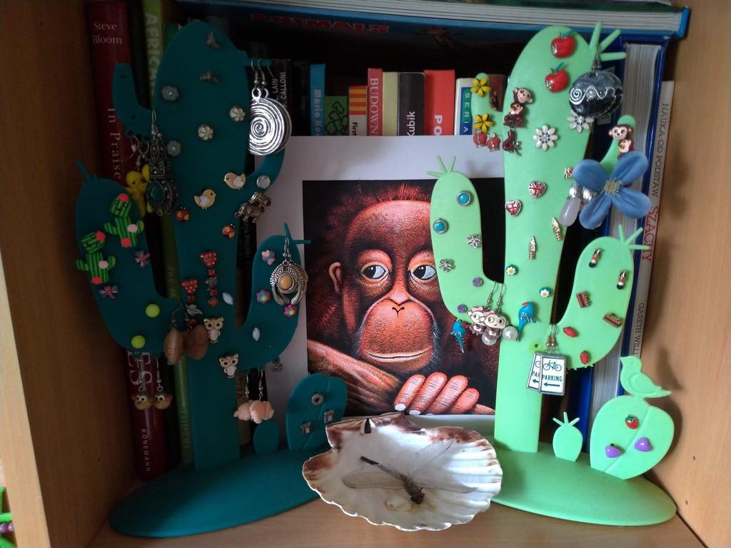 Małpy kolekcja. Obraz z małpą postawiony na półce. Po bokach dwa ozdobne wieszaki na biżuterię w kształcie kaktusa.