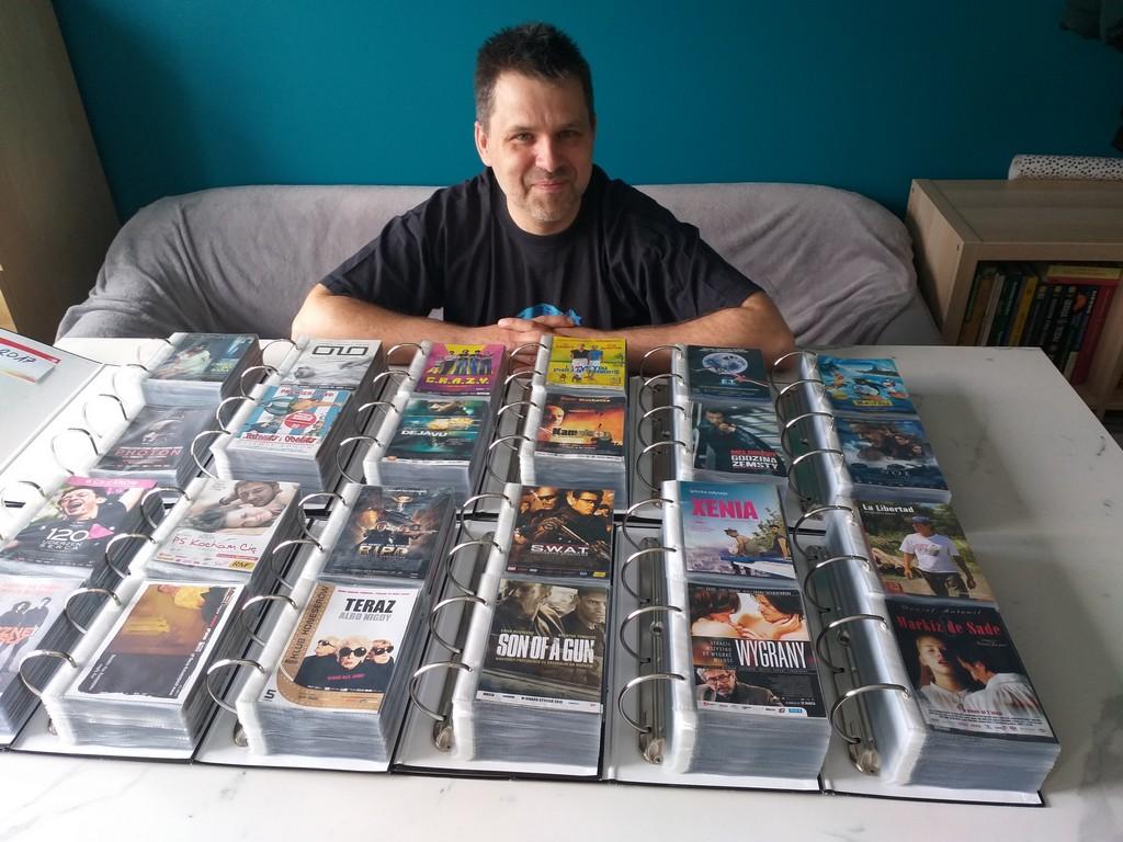 ulotki filmowe kolekcja. Mężczyzna siedzący przed segregatorami ze zbiorami ulotek