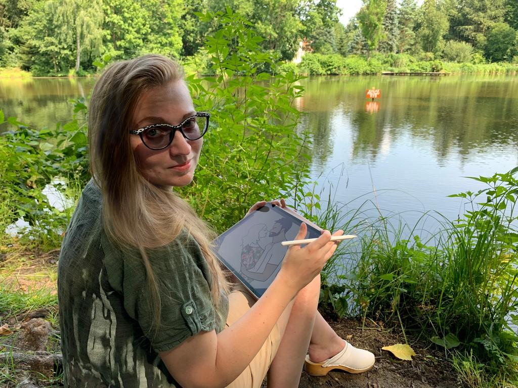 Kasia Trepkowska rysowniczka. Kobieta siedząca nad jeziorem. W ręce trzyma tablet.
