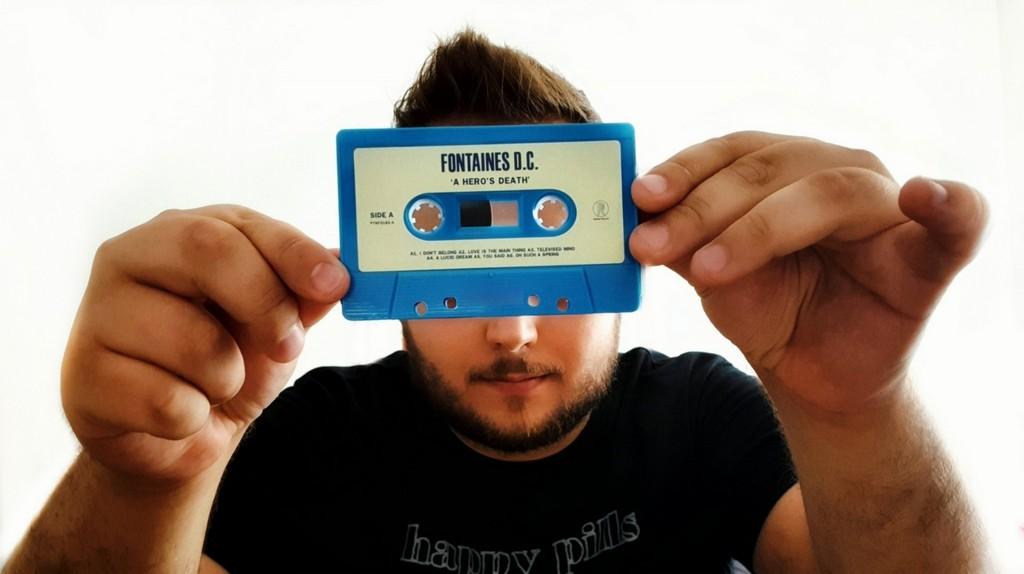 Mężczyzna trzymający przed sobą kasetę