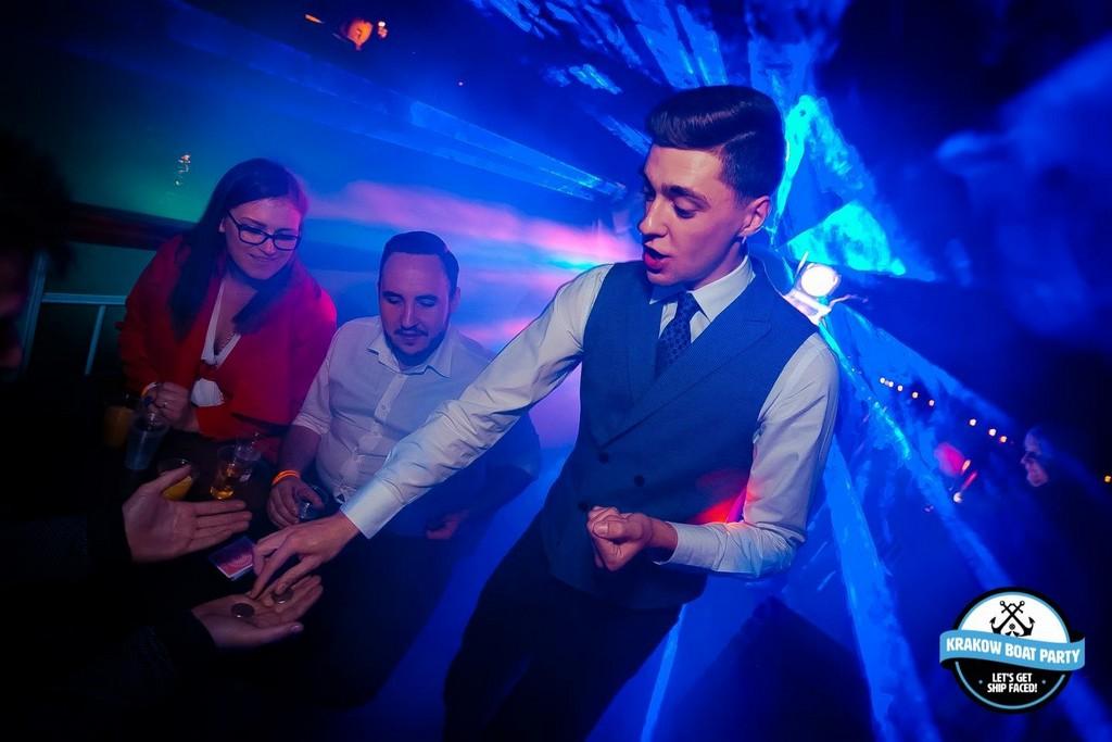 Pokaz magii w klubie. Mężczyzna stojący przy dwóch osobach, na dłoni kładzie monety. Magia