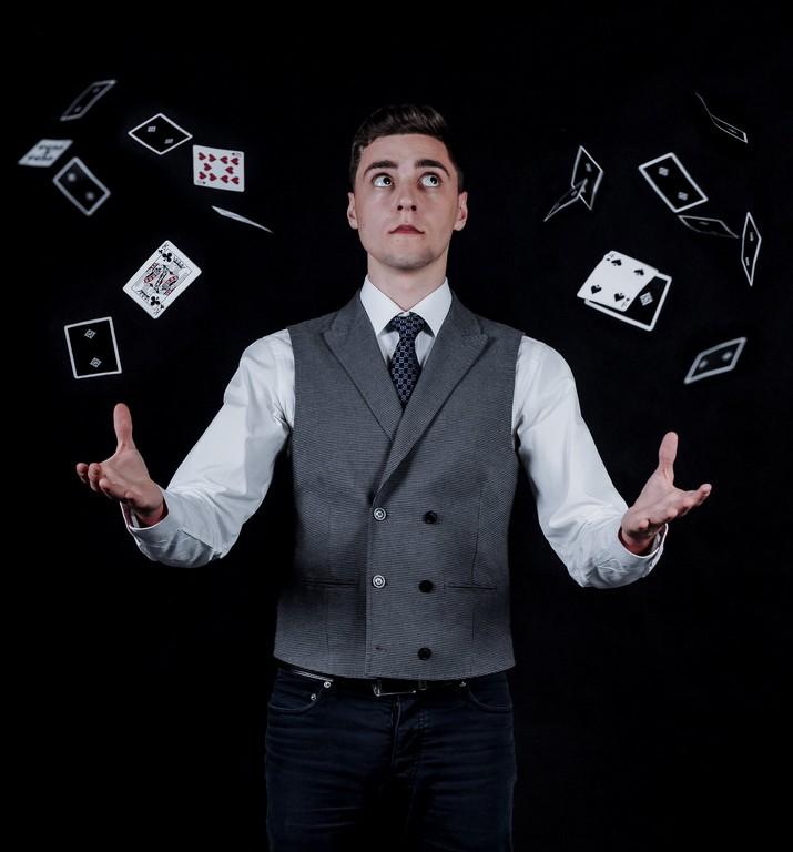 Paweł Wołodko. Mężczyzna stojący z rozłożonymi rękami, wokół niego lewitujące karty. Magia - pokaz