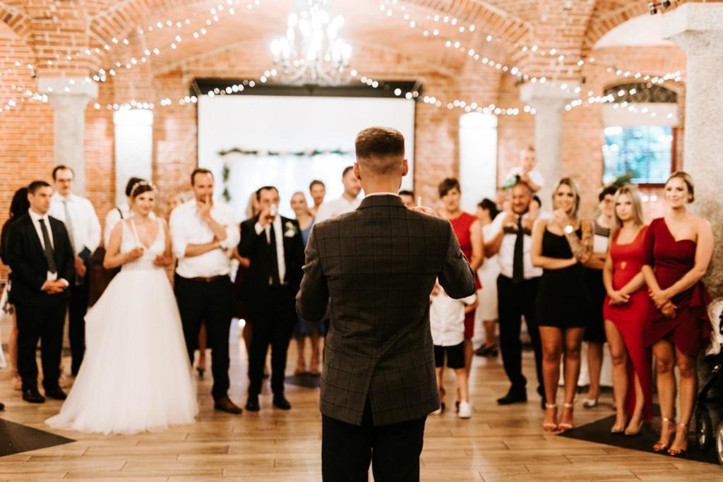 Wesele, pokaz magii. Na pierwszym planie mężczyzna odwrócony tyłem, przed nim goście weselni.