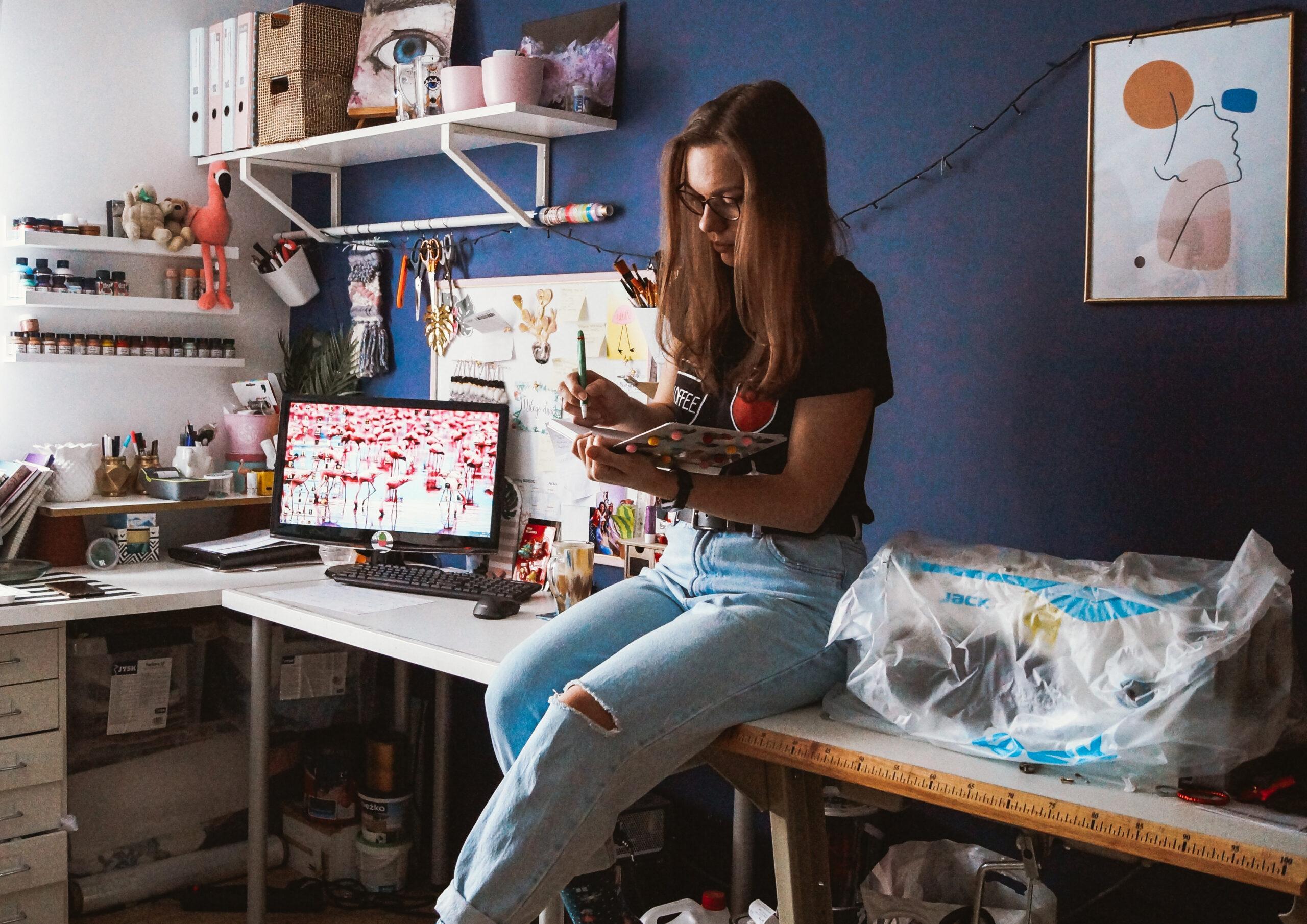 Kobieta siedząca na biurku, rysująca w zeszycie