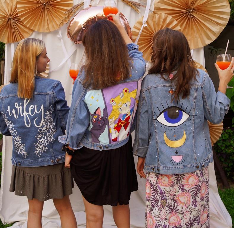 Trzy kobiety stojące tyłem. Na sobie mają ubrane ręcznie malowane jeansowe kurtki.