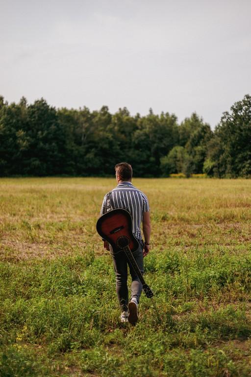 Chłopak z gitarą idący tyłem po polach - Nikodem Kurach