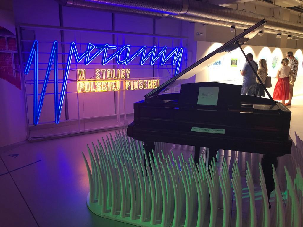 Duży napis Muzeum Polskiej Piosenki w Opolu. Obok fortepian.